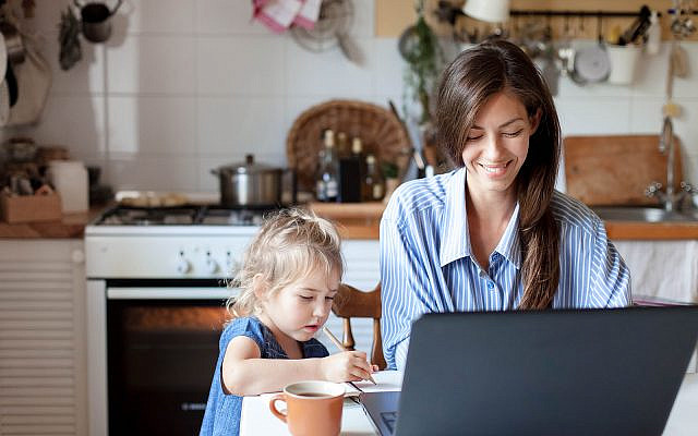 Working mom works from home office with kid. Happy mother and daughter. Woman and cute child using laptop. Freelancer workplace in cozy kitchen. Female business, career. Lifestyle family moment.