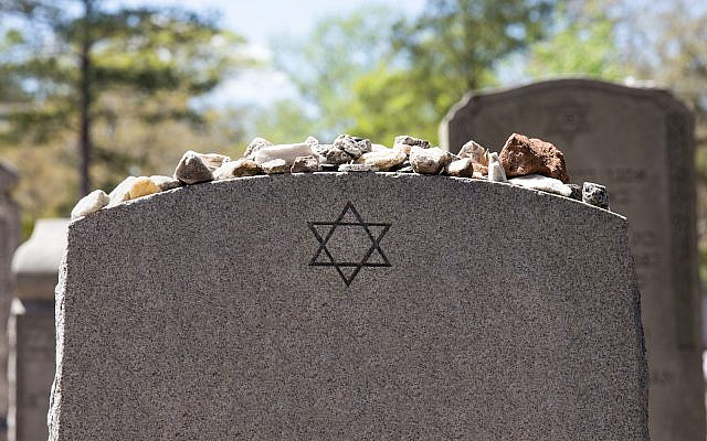 Headstone in a Jewish cemetery with Star of David and memory stones.  (iStock)