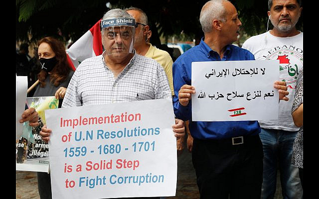 """Anti-Hezbollah protesters hold placards during a sit-in against Hezbollah and Iran in front of the French ambassador's house, in Beirut, Lebanon, Tuesday, July 14, 2020. The Arabic placard reads:""""No to the Iranian occupation, yes to disarmed Hezbollah weapons."""" (AP Photo/Hussein Malla)"""
