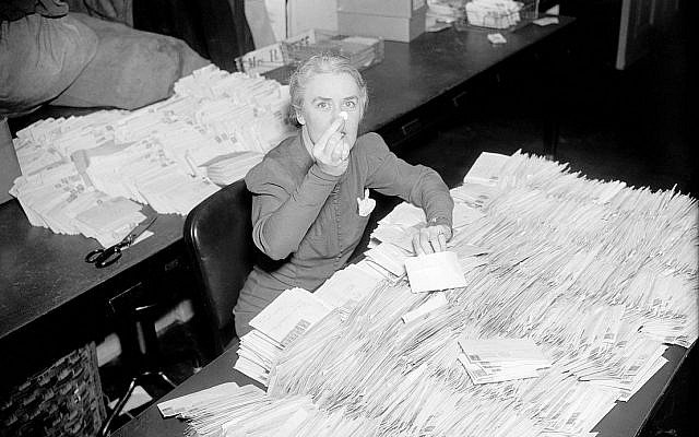 Missy (Margaret) LeHand, secretary to President Franklin D. Roosevelt, with the morning mail arriving at the White House in response to an appeal to donate dimes to fight infantile paralysis as a way of celebrating the president's birthday — the first March of Dimes campaign, Washington, DC, January 28, 1938. (Harris & Ewing, Library of Congress, Wikipedia)