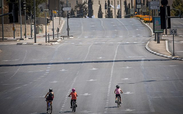 People ride their bicycles along the empty road in Jerusalem, on Yom Kippur, the Day of Atonement, and the holiest of Jewish holidays, October 9, 2019. (Yonatan Sindel/Flash90)