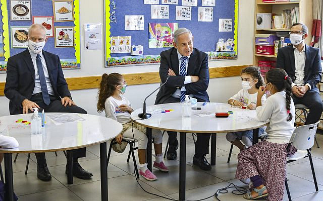 Prime Minister Benjamin Netanyahu (C) and Education Minister Yoav Gallant (L) visit Israeli kids on their first day of school in the Mevo Horon settlement on September 1, 2020. (Marc Israel Sellem/ POOL)