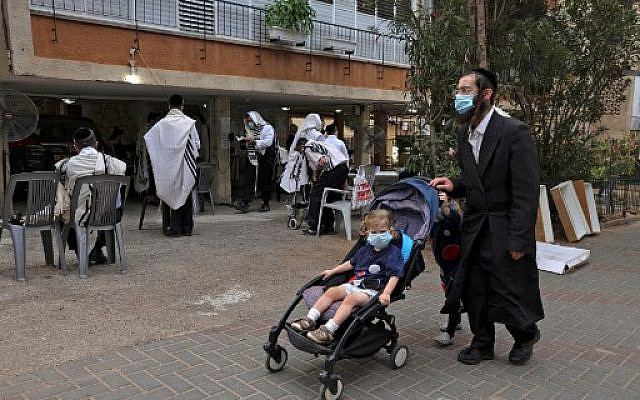 Men praying outside a synagogue to prevent or diminish outbreaks of COVID-19, in the ultra-Orthodox city of Bnei Brak, September 6, 2020. (MENAHEM KAHANA/ AFP)
