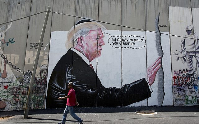 A mural resembling the work of elusive artist Banksy depicting President Donald Trump wearing a Jewish skullcap, is seen on Israel's West Bank separation barrier in the West Bank city of Bethlehem, Friday, Aug. 4, 2017. (AP Photo/Nasser Nasser)