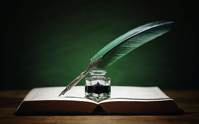 Quill pen, inkwell, and book. (iStock)