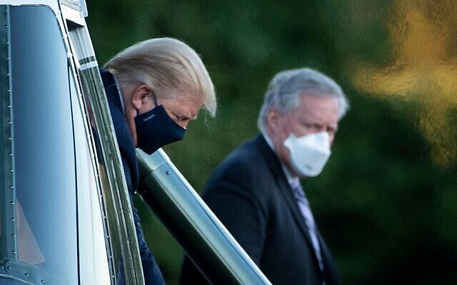 White House Chief of Staff Mark Meadows (R) watches as US President Donald Trump walks off Marine One while arriving at Walter Reed Medical Center in Bethesda, Maryland on October 2, 2020. - President Donald Trump will spend the coming days in a military hospital just outside Washington to undergo treatment for the coronavirus, but will continue to work, the White House said Friday (Photo by Brendan Smialowski / AFP)