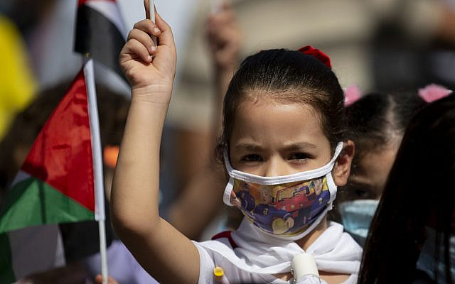 A Palestinian girl wearing a protective face mask amid the coronavirus pandemic takes part in a rally in support of Palestinian President Mahmoud Abbas in the West Bank town of Tubas, Sunday, Sept. 27, 2020. (AP Photo/Majdi Mohammed)