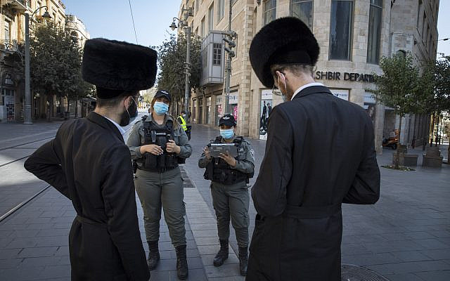Israeli border police officers check citizents on Jaffa Street in downtown Jerusalem on October 7, 2020, during a nationwide lockdown to prevent the spread of COVID-19. (Nati Shohat/Flash90)