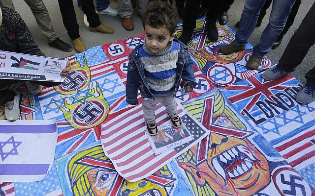 A Palestinian child stands on the illustrations of the British Union flag, the Israeli flag, and an American flag during a protest against the American peace plan in the Middle East, in Gaza City. (Photo by Mahmoud Issa / SOPA Images/Sipa USA via Jewish News)
