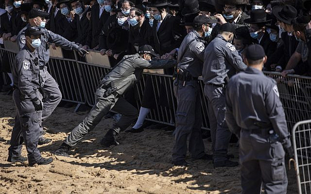 Israeli police try to control a crowd of mourners during the funeral of Rabbi Mordechai Leifer, the latest in a string of clashes between security forces and ultra-Orthodox Jews violating a national coronavirus lockdown order, in the port city of Ashdod, Israel, October 5, 2020. (AP Photo/Tsafrir Abayov)