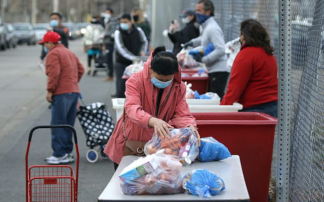 A person picks up some of the donated produce at the American Red Cross Boston Food Pantry Thanksgiving meal distribution in Boston on Nov. 21, 2020. (Jonathan Wiggs/The Boston Globe via Getty Images via JTA)
