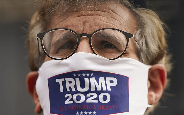 A member of the Jewish Orthodox community wears a mask supporting President Donald Trump, Wednesday, Oct. 7, 2020, in Borough Park, Brooklyn, New York. (AP Photo/John Minchillo)