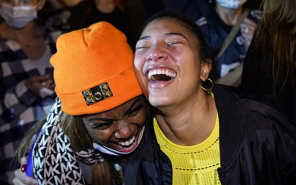 Lisa Alcindor, left, and Angelique McKenna, watch and react to a victory speech by President-elect Joe Biden while celebrating at Black Lives Matter Plaza, Saturday, Nov. 7, 2020, in Washington. (AP Photo/Jacquelyn Martin)