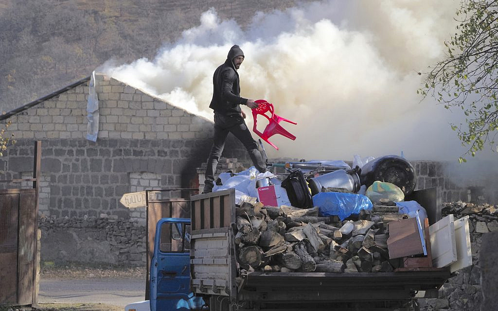 A man loads possessions on his truck after setting his home on fire, in an area once occupied by Armenian forces but soon to be turned over to Azerbaijan, in Karvachar, the separatist region of Nagorno-Karabakh, on Friday, Nov. 13, 2020. Under an agreement ending weeks of intense fighting over the Nagorno-Karabakh region, some Armenian-held territories adjacent to the region are passing to Azerbaijan. (AP Photo/Dmitry Lovetsky)