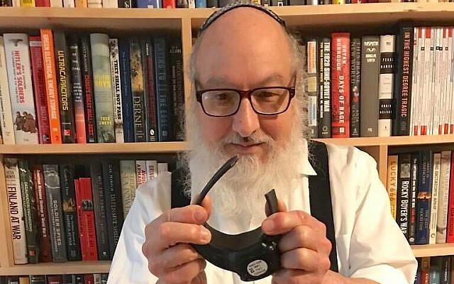 Jonathan Pollard holding his recently cut electronic monitor bracelet on November 20, 2020. (Adi Ginzburg/Justice for Jonathan Pollard)