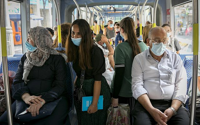 Passengers wearing face masks for fear of the coronavirus ride the light rail in in Jerusalem on April 21, 2020 (Olivier Fitoussi/Flash90)
