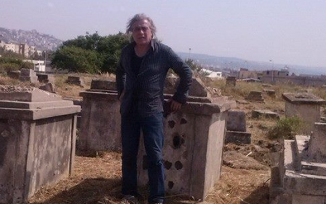 Caretaker of the Sidon Jewish cemetery Nagi Zeidan stands in front of a tombstone riddled with bullet holes (Photo: courtesy)
