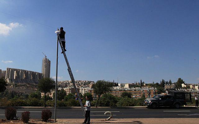 Checking an eruv in Jerusalem the old-fashioned way. (Nati Shohat/Flash90)