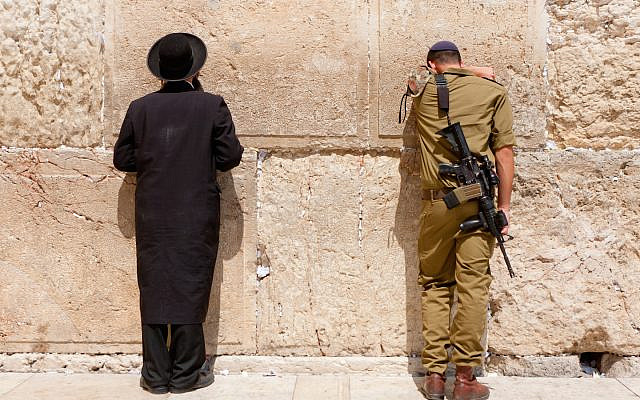 Jerusalem, Israel - July 18, 2010: Soldier and Orthodox jews pray at the wailing wall. Jerusalem with people.