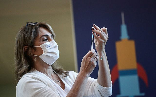 An Israeli medical worker holds a coronavirus vaccination, at Tel Aviv Sourasky Medical Center on December 20, 2020 (Miriam Alster/Flash90)