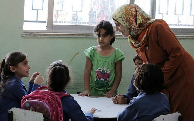 A Jordanian teacher talks to Syrian refugee students at a school in Amman, Jordan, September 1, 2016. (AP Photo/Ahmad Alameen)