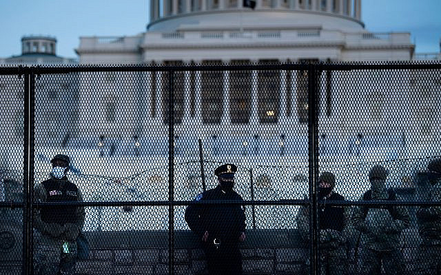 A Capitol police officer stands with members of the National Guard behind a crowd control fence surrounding Capitol Hill a day after a pro-Trump mob broke into the Capitol building, Jan. 7, 2021 (Brendan Smialowski/AFP via Getty Images)