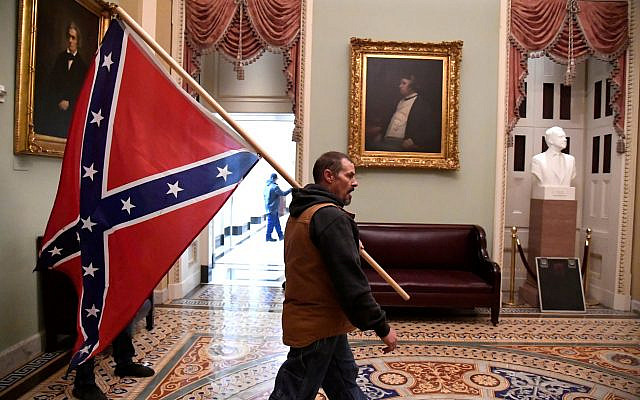 A supporter of President Donald Trump carries a Confederate battle flag on the second floor of the U.S. Capitol near the entrance to the Senate after breaching security defenses, in Washington, U.S., January 6, 2021.         REUTERS/Mike Theiler     TPX IMAGES OF THE DAY