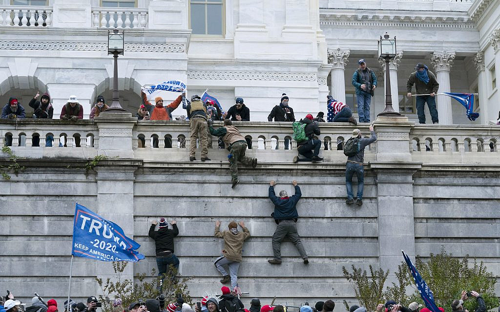 Supporters of US President Donald Trump climb the west wall of the the US Capitol on Wednesday, Jan. 6, 2021, in Washington. (AP Photo/Jose Luis Magana)