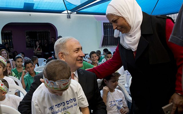 Illustrative: Prime Minister Benjamin Netanyahu poses for a photograph with pupils on the first day of school in the Israeli Arab town of Tamra, September 1, 2016. (AP/Sebastian Scheiner)