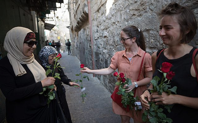 Illustrative: Israelis pass out roses to Arabs in the Muslim quarter of Jerusalem's old City, during Jerusalem Day. May 24, 2017.  (Nati Shohat/Flash90)