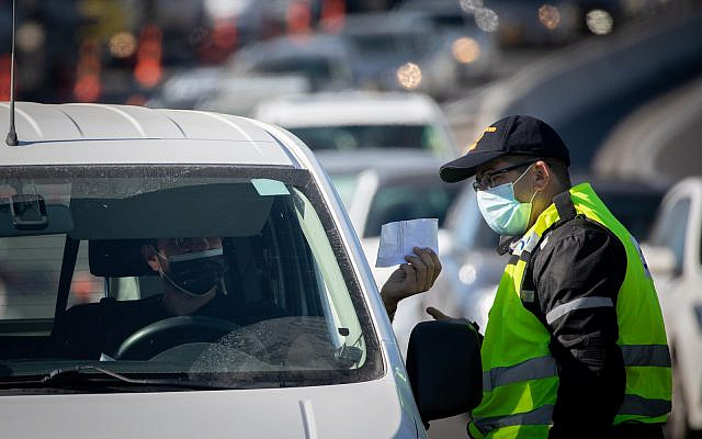Police at a temporary roadblock on Road Number 1 outside Jerusalem on January 8, 2021, during a 3rd nationawide full lockdown, in an effort to prevent the spread of the Coronavirus. (Yonatan Sindel/Flash90)