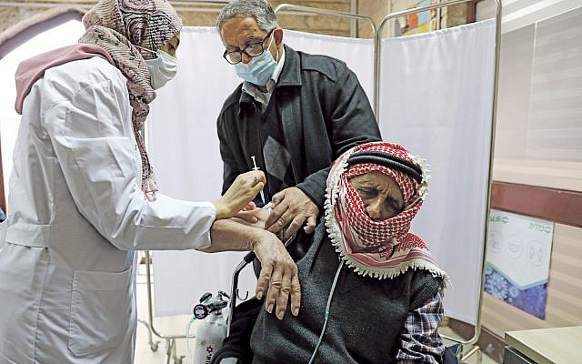 A Palestinian man is helped by his son as he receives a vaccination against the coronavirus disease (COVID-19) as Israel continues its national vaccination drive, in East Jerusalem December 23, 2020. REUTERS/Ammar Awad via Jewish News