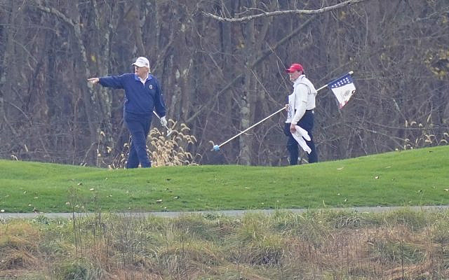 US President Donald Trump, left, gesturing while playing golf at Trump National Golf Club in Sterling, Virginia, November 15, 2020. (Manuel Balce Ceneta/AP)