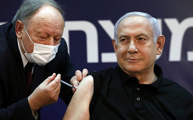 Israeli Prime Minister Benjamin Netanyahu receives a coronavirus vaccine at the Sheba Medical Center, the country's largest hospital, in Ramat Gan near the coastal city of Tel Aviv, on December 19, 2020. - Netanyahu, 71, and Israel's health minister were injected with the Pfizer-BioNTech vaccine live on TV at Sheba Medical Center. Each recipient must receive a booster shot in three weeks for optimal protection from the novel coronavirus. (Photo by AMIR COHEN / POOL / AFP)