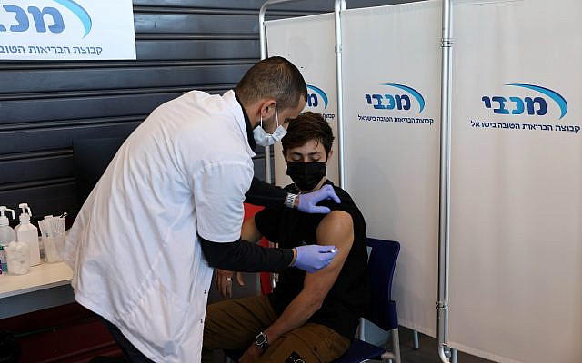 A teenager receives a vaccination against the coronavirus disease (COVID-19), in Tel Aviv, Israel, January 24, 2021. REUTERS/Ronen Zvulun