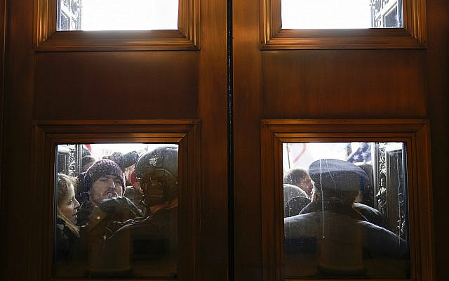 US Capitol Police try to hold back protesters outside the east doors to the House side of the US Capitol, January 6, 2021. (AP Photo/Andrew Harnik, File)