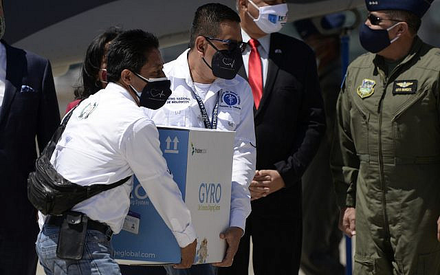 Health workers carry a box of 5,000 doses of COVID vaccine donated by Israel arriving at the Air Force base in Guatemala City, Feb. 25, 2021. (Johan Ordonez/AFP via Getty Images)