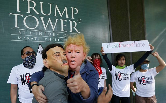 Protesters, with one wearing a Donald Trump mask and another with an Adolf Hitler mask, embrace as others display a #lovetrumpshate hashtag during a brief picket at the Trump Tower hours after Trump was sworn in as the 45th President of the United States Jan. 21, 2017 in the financial district of Makati city east  Manila, Philippines.(AP Photo/Bullit Marquez)