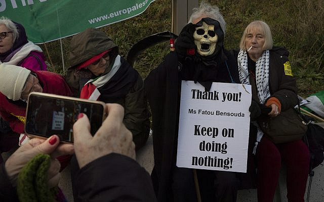 A woman takes a picture of the Grim Reaper holding a sign referring to Chief Prosecutor Fatou Bensouda during a demonstration outside the International Criminal Court, ICC, urging the court to prosecute Israel's army for war crimes in The Hague, Netherlands, November 29, 2019. (AP/Peter Dejong)