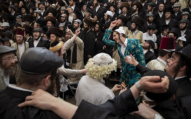 Illustrative: Ultra-Orthodox men celebrate Purim in Jerusalem's Mea Shearim neighborhood, on March 11, 2020. In retrospect, it may have been a super-spreader event. (AP Photo/Oded Balilty)