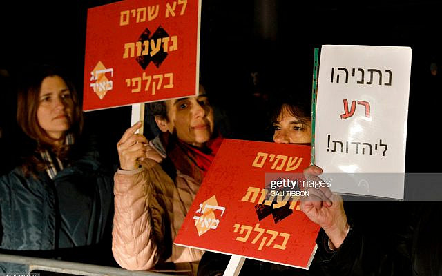 """Israeli demonstrators carry placards (which read in Hebrew: No to putting racism in the ballot box) during a protest against the extreme right-wing Kach movement members joining the Knesset (Israeli parliament), under the slogan """"a Jewish voice against Kahanism"""" on March 2, 2019 in front of Prime Minister Netanyahu's residency in Jerusalem. - The Kach movement, founded by Rabbi Meir Kahane who was assassinated in 1990 in the US, has been banned by the Israeli government for being """"racist"""" and """"anti-democratic"""" in 1994. (Photo by GALI TIBBON / AFP)        (Photo credit should read GALI TIBBON/AFP via Getty Images)"""
