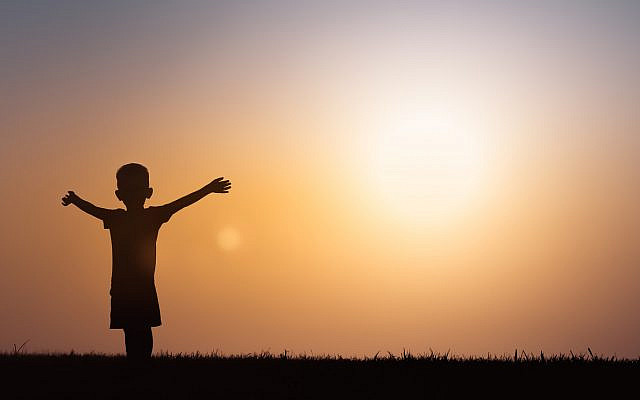 A young boy, reaching out his arms at sunset. (iStock)
