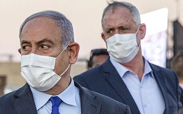 (FILES) In this file photo taken on June 25, 2020, Israeli Prime Minister Benjamin Netanyahu (L) and his coalition partner Defence Minister Benny Gantz (R), both clad in masks due to the COVID-19 coronavirus pandemic, arrive to attend a graduation ceremony for new pilots in Hatzerim air force base near the southern Israeli city of Beersheba. - Israel's defence chief Benny Gantz has established a government commission to probe the country's purchase of German submarines, an affair allegedly involving associates of premier Benjamin Netanyahu, his ministry announced. (Photo by Ariel Schalit / POOL / AFP)