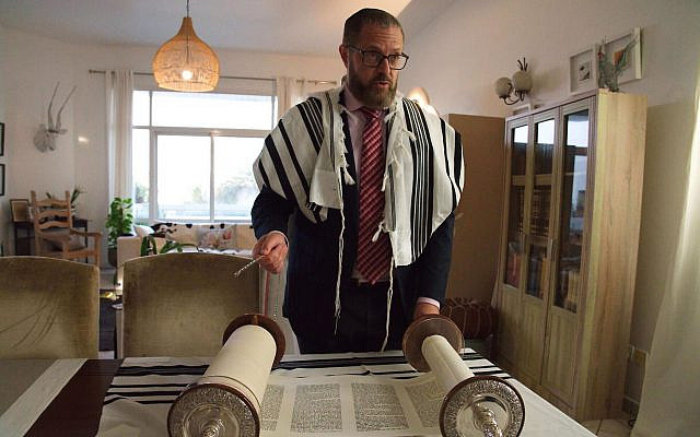 Alex Peterfreund, a co-founder of Dubai's Jewish community, its cantor, and an AGJC board member with a Torah scroll in Dubai, United Arab Emirates, August 16, 2020. (AP Photo/Jon Gambrell)