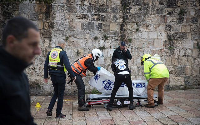 Police and medical personnel near the body of terrorist at the scene of an attempted stabbing attack at the Lions Gate in Jerusalems Old City, February 22, 2020. (Yonatan Sindel/Flash90)