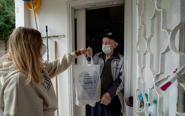 An Israeli volunteer gives away food package to a holocaust survivor in Ramat Gan, January 29, 2021. Photo by Chen Leopold/Flash90
