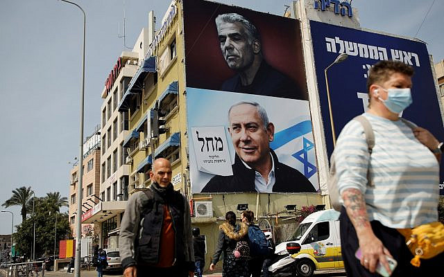 People walk near a Likud party election campaign banner depicting Israeli Prime Minister Benjamin Netanyahu and his challenger, Yesh Atid party leader Yair Lapid, ahead of the March 23 ballot, in Tel Aviv, Israel March 14, 2021. REUTERS/Corinna Kern