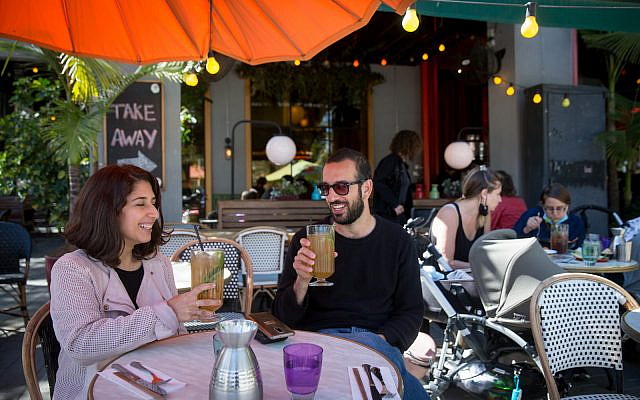 Customers enjoy dining at restaurants after they were recently re-opened, in Tel Aviv on March 07, 2021. (Miriam Alster/Flash90)
