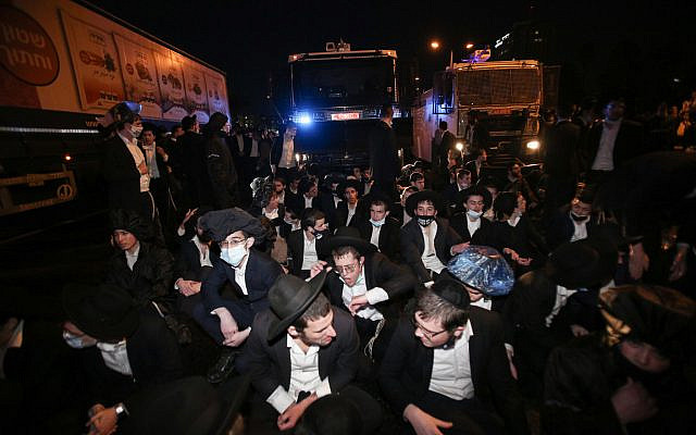 Ultra-Orthodox Jews clash with police as they protest against the arrest of ultra-Orthodox Jewish men who failed to comply with their army draft, in Bnei Brak, December 27, 2020. (Noam Revkin Fenton/Flash90)