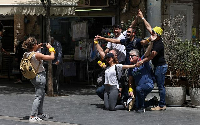 People pose for a picture on a street in Jerusalem, on April 18, 2021, after Israeli authorities announced that face masks for COVID-19 prevention were no longer required outdoors. (Menahem Kahana / AFP)